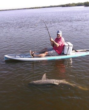 Jim McGuire with a hefty bull shark he fought from paddle board with Capt. Todd Geroy.